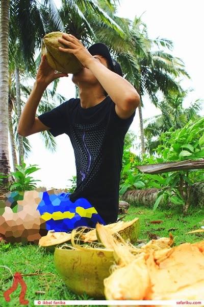 Minum kelapa di pantai