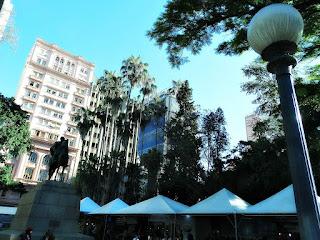 Bancas da Feira do Livro na Praça da Alfândega (Porto Alegre) - Clube do Comércio, à esquerda