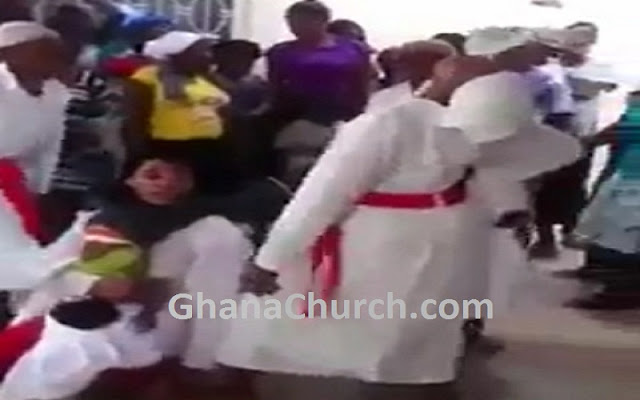 Church members look on as leader throws little girl around
