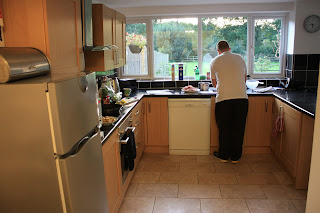 Picture of kitchen, where Neil is making dinner. Tiled floor and open layout.