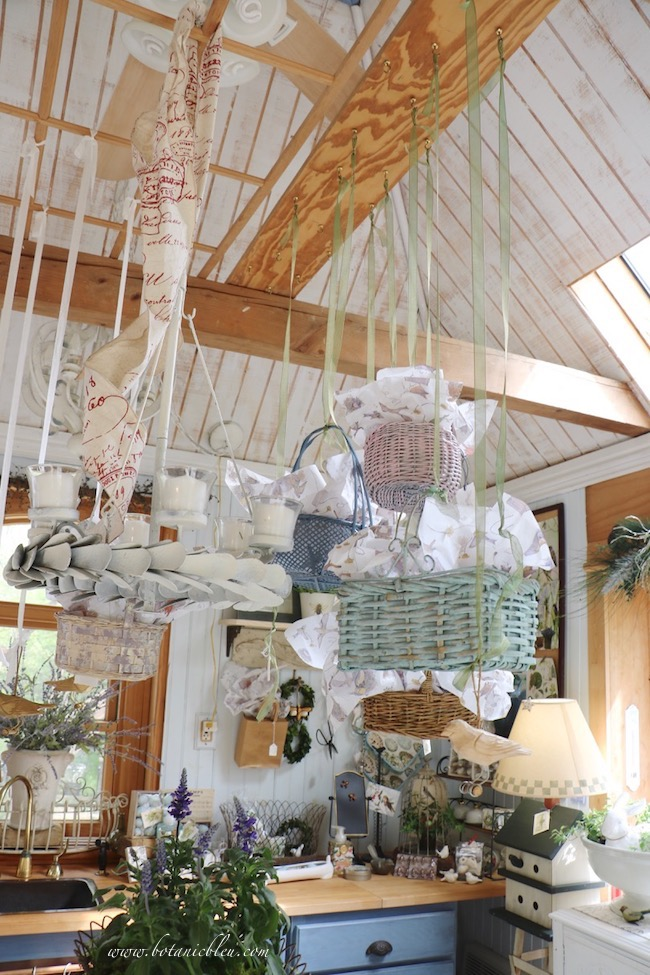 Spring baskets in pastel colors hang from a board between two ceiling beams in the garden shed