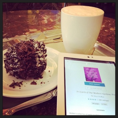 A white Kobo with the Scribd page for In Search of Our Mothers' Gardens on its open screen appears between a rum ball encrusted in chocolate curls and a foam-topped latte. All three items rest on a silver tea tray.