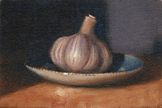 Oil painting of a garlic bulb on a blue and white saucer.
