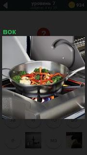 Приготовление еды на газовой плите вок в сковородке на кухне