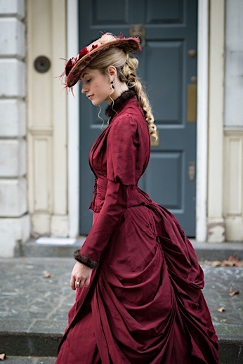 Red/maroon/burgundy color walking dress (bodice with matching skirt) with bustle in the back, worn with a feathered wide brim hat. Victorian daytime clothing for women.