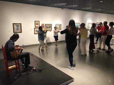 En la sede de la Fundación Cajasol y con los cuadros expuestos de fondo, el guitarrista toca mientras que la profesora y participantes bailan.