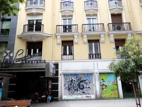 Fachada de Fuencarral 135, a la izquierda la cafetería Somosierra, cerrada, y una indigente cobijándose. Cierres de tiendas.