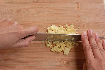 Rock knife over pile of sliced ginger