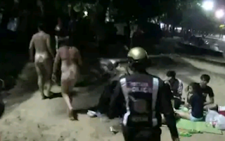 Naked man and woman paraded on the street by the police
