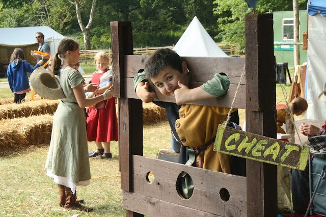 child in stocks medieval festival england