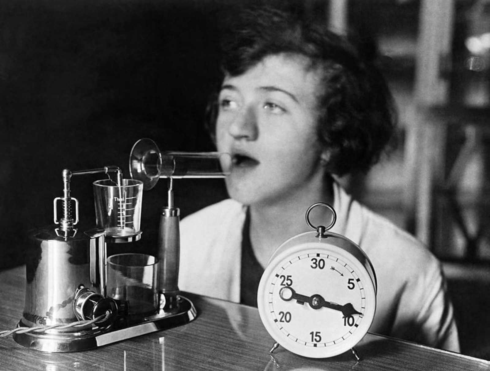 Una mujer que usa un aparato de inhalación eléctrico que produce una niebla medicada utilizada en el tratamiento de resfriados e influenza, alrededor de 1929.