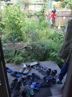 a gathering of shoes outside an open door that looks onto a green garden