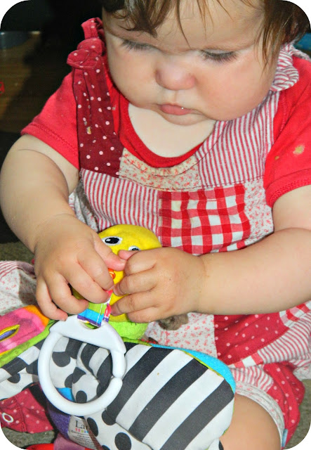 Baby girl  playing with Freddie the Firefly TOMY Lamaze