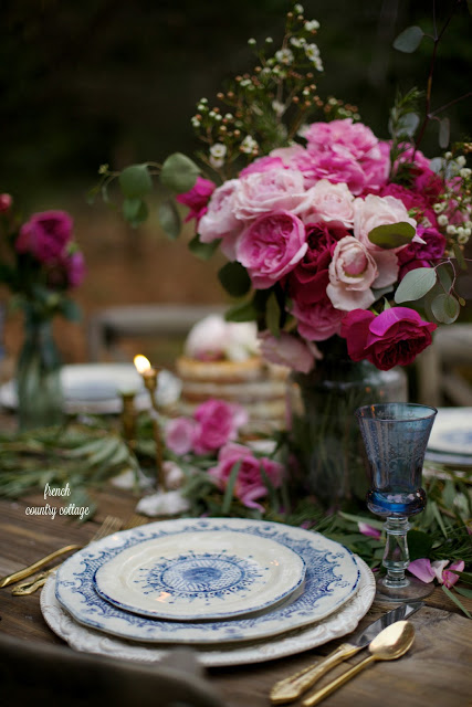 An outdoor table is romantically dressed with pink blossoms and blue china, golden silverware to celebrate valentines day