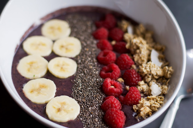 The Acai Bowl in a white bowl and topped with banana, chia seeds, raspberries, and granola.
