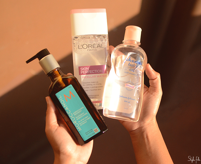 Image of a woman's hands holding the Moroccan Oil Treatment Original bottle, L'Oreal Paris Skin Perfection Micellar Water and Johnson's Baby Oil against a brown background in sunlight
