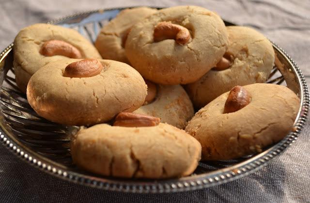 koekjes met kardemom op een Oosters zilveren schaaltje met rasterpatroon. De koekjes zijn gegarneerd met een cashewnoot en hebben een beetje een Oosters uiterlijk