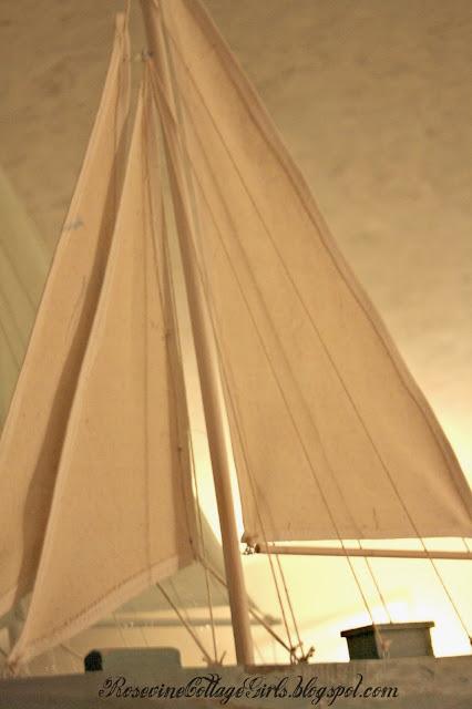close up of a model of a blue sailboat on a fireplace mantle | sea side Living room \ seaside livingroom | rosevinecottagegirls.com