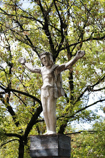Statue of crucified Jesus against the branches of a tree