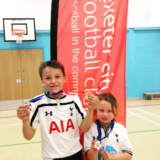 Showing off medals from the Exeter City Football in the Community summer holiday course