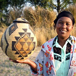 Zulu weaver Nomkhosi Nkosi holding one of her baskets