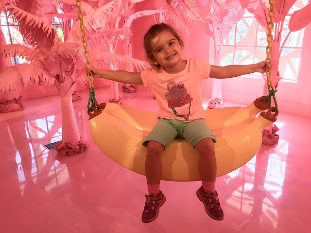 Toddler girl sitting on a swing shaped like a banana