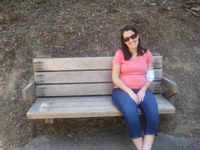 Pregnant Rachel sitting on a park bench wearing an orange shirt and sunglasses