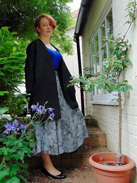Black cocoon coat, blue top and grey floral midi skirt