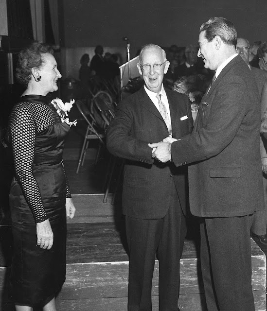 Ruth Beers Arnold observes as husband Earl J. Arnold shakes hands with unidentified gentleman