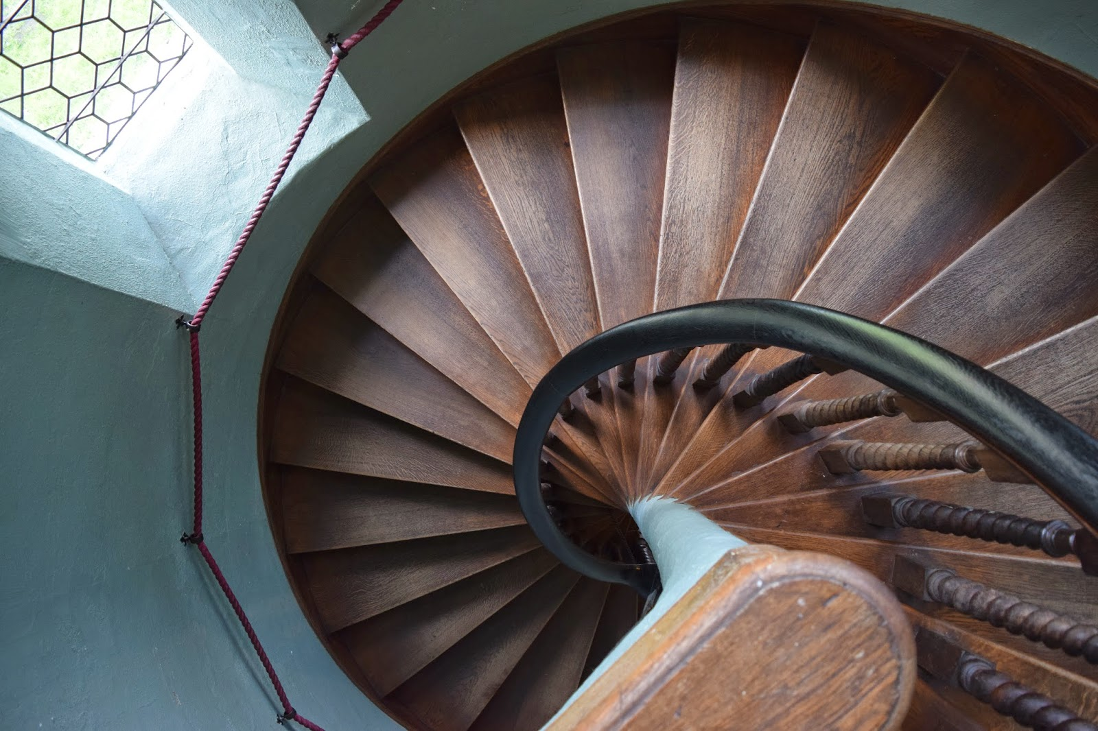 looking down a spiral staircase inside warwick castle