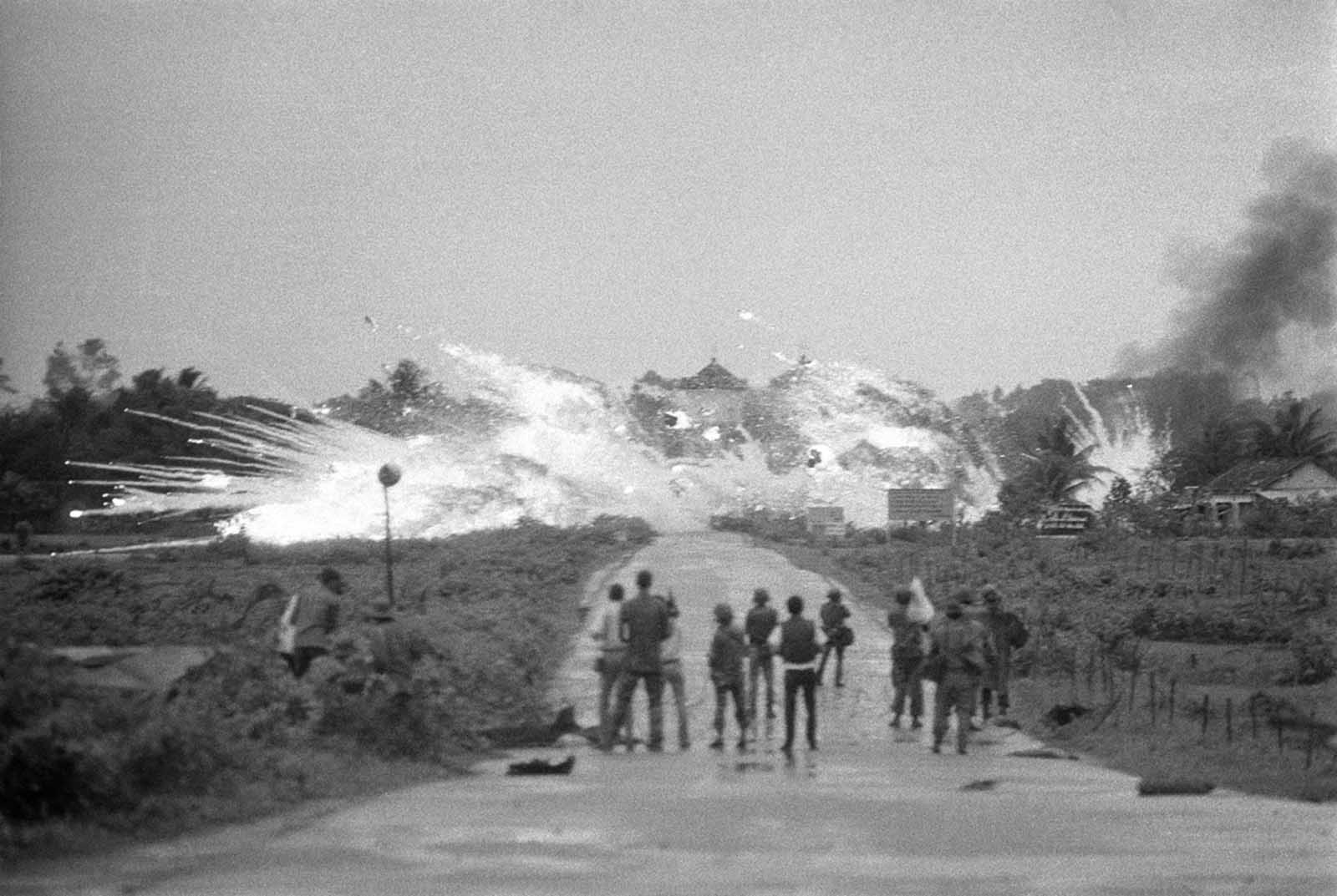 Bombs with a mixture of napalm and white phosphorus jelly dropped by Vietnamese AF Skyraider bombers explode across Route 1, amid homes and in front of the Cao Dai Temple in the outskirts of Trang Bang, on June 8, 1972. In the foreground are Vietnamese soldiers and news and cameramen from various international news organizations who watch the scene.