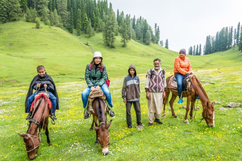 Majid Khan and his son with my Family pose for a photo while Horses feast on flowers and grass of Bungus