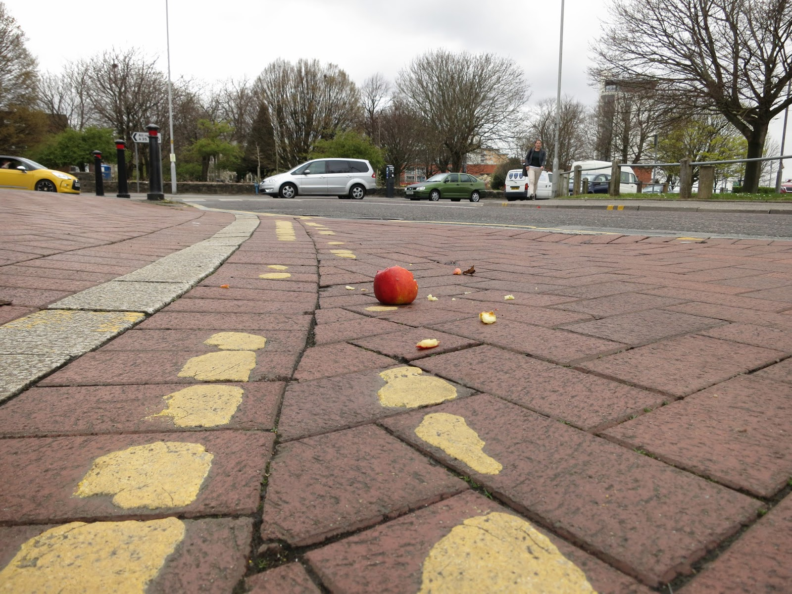 Broken apple on brick road with yellow lines and cars crossing.