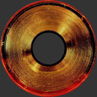 [Image: A high-resolution photograph taken tangentially towards the record. Grooves are clearly visible as darker lines, and even the recorded signal can be seen as oscillations in the grooves. The end of the record seems to be silent.]