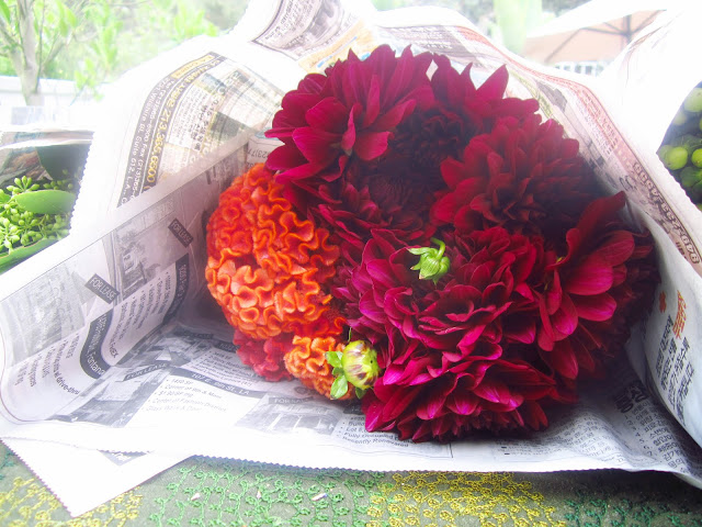bouquet of dahlias and coscums wrapped in newspaper on a deck table