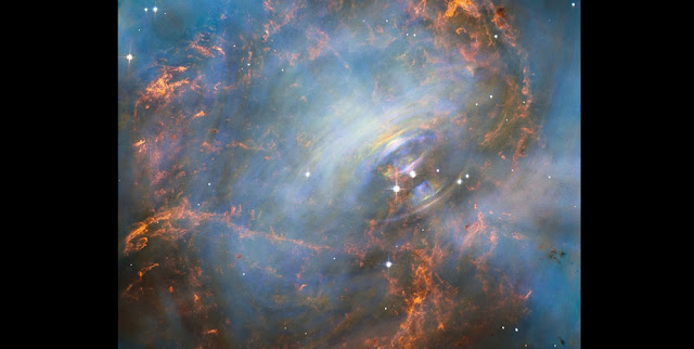 While many other images of the famous Crab Nebula have focused on the filaments in the outer part of the nebula, this image shows the very heart of the Crab Nebula including the central neutron star — it is the rightmost of the two bright stars near the centre of this image.  The rapid motion of the material nearest to the central star is revealed by the subtle rainbow of colours in this time-lapse image, the rainbow effect being due to the movement of material over the time between one image and another.  Credit: NASA, ESA