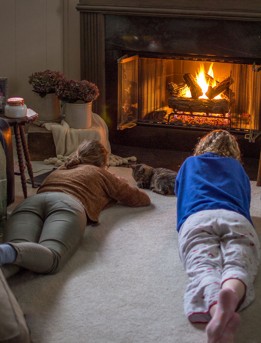 girls and kitty lying in the floor on the carpet next to a fire