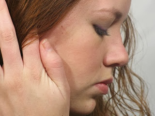 A very shy girl touching her hair