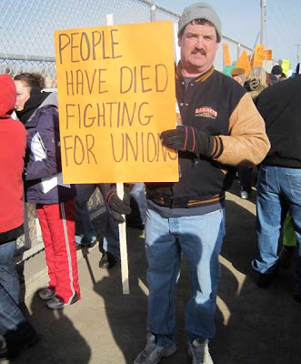 Man with sign reading People have died fighting for unions