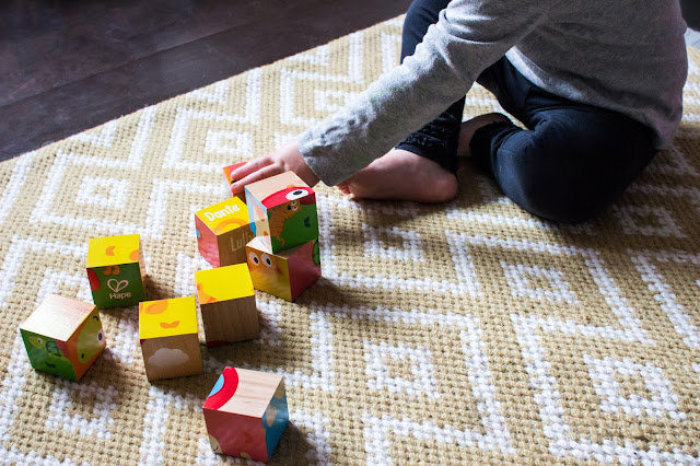 A little person playing with colourful blocks with pictures on