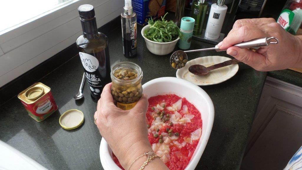 Alcaparras en la ensalada de láminas de bacalao