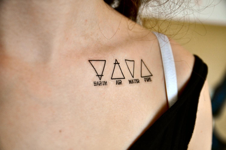 Mujer con tatuajes de triángulos en la clavícula