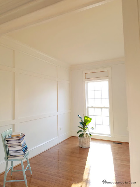 living room with architectural molding featured wall