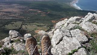 Jemand sitzt auf einem hohen Felsen, man sieht nur die Schuhe und einen weiten Blick ins grüne Tal