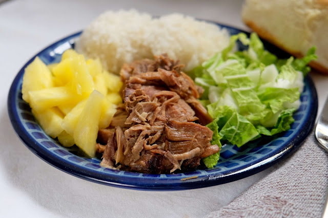 a plate of slow cooker kalua pig with fresh pineapple, hot cooked rice, sweet Hawaiian roll, and cabbage