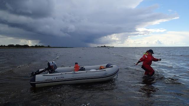 Pelastautumispukuinen henkilö kahlaa ja vetää kumivenettä perässään