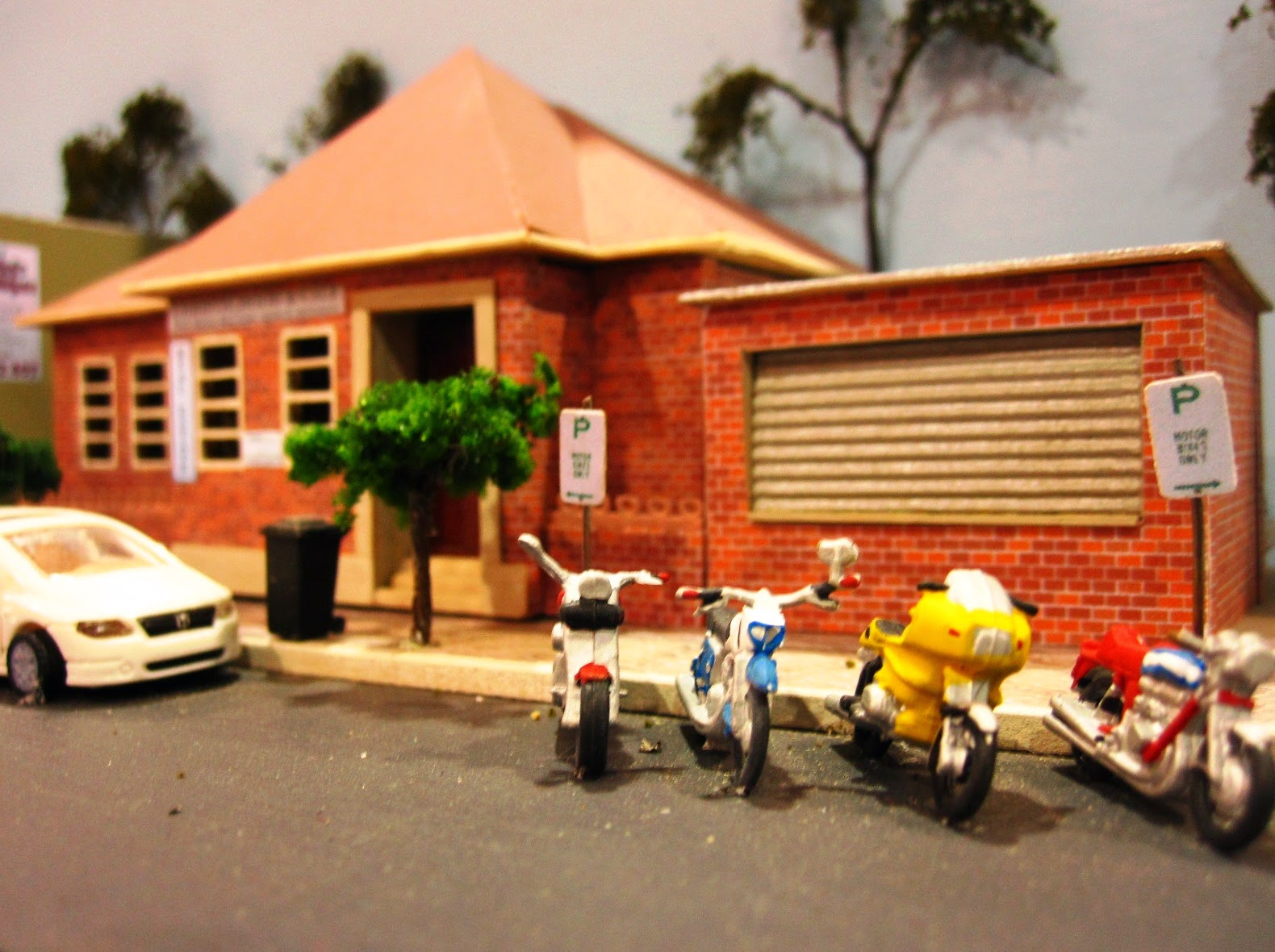 Quarter inch scale modern Australian town street scene with council building and motorcycles parked outside.