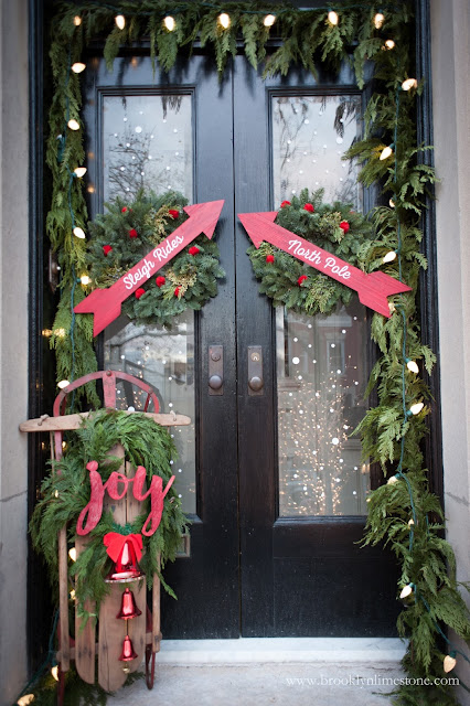 Christmas front door decorated with two wreaths with red arrows