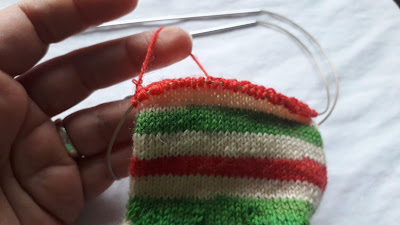 A hand knit sock in red, green and white, still on the needles.  To the left of the photo is a hand holding a loop of red yarn from behind the top of the sock.