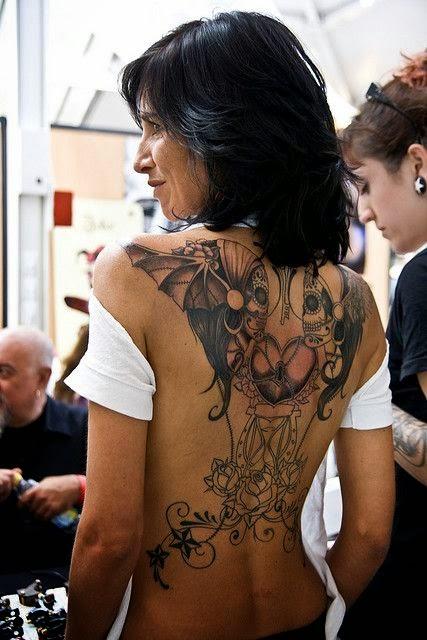 mujer de pelo moreno con tatuaje en la espalda, esta en un puesto en una convencion de tatuajes